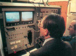 Surveillance de la tenue du pantographe au cours de l'essai, à l'aide de deux écrans reliés à des caméras placées sur le toit de la rame. Sur la vue de détail, on remarque au bas de l'écran les indications kilométrique (156,8) et de vitesse (366). © CAV-SNCF - P. Olivain